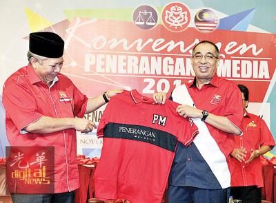 """通讯与多媒体部长拿督斯里沙烈赛益(右)接领安努亚慕沙赠送的""""马来西亚宣传""""T恤。"""
