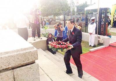 """林冠英受邀出席""""第15届英雄纪念日"""",并在旧关仔角的世界大战纪念碑前献花。"""