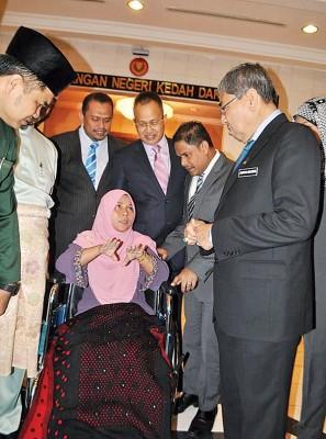 阿末巴沙(右)慰问抱伤坐著轮椅出席州议会的卡玛诺丽雅。