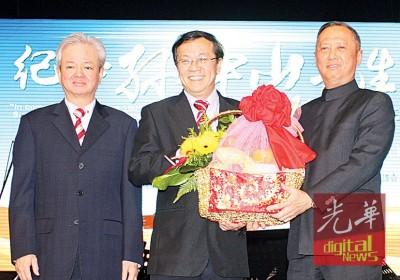 何国忠(左2起)从陈志勇的手上接收水果礼篮。左为古润金。