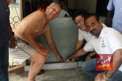 吴江水(左)示范如何把粘土塞在铁门与地板的缝隙间,防止水渗入住家,旁为亚依淡州议员黄汉伟和武吉牛汝莪国会议员蓝卡巴星。