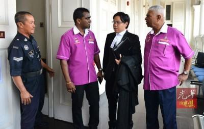 安美嘉之臂膀在法庭外与 前面槟州志愿巡逻队协调员谈论。