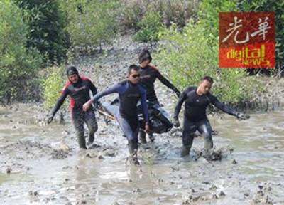 搜寻队从沼泽中抬出死者尸体。
