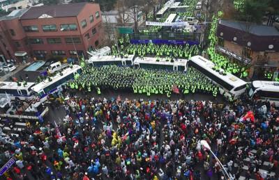 韩国民众周六游行逼近到距青瓦台仅200公尺处,警方以警车筑车墙戒备。(法新社照片)