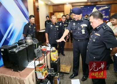 阿玛星(右2)向媒体展示警方起获的行乞工具。