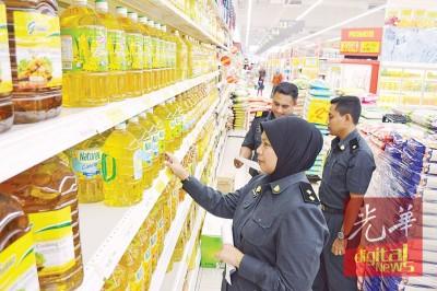 玻州市消局执法员检查州内超市的食用油供应。