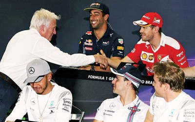 于F1巴西站赛前发布会上,国际汽车联合会赛事主管查理怀汀和维泰尔握手和解。