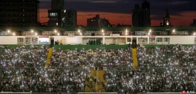 球迷为罹难球员挥动手机白光照耀天堂之路。