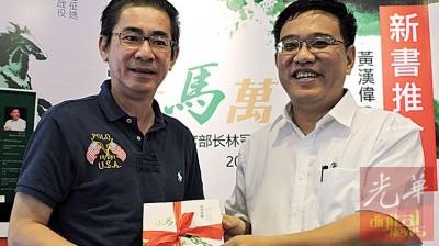 黄汉伟赠送新书给《光华日报》,由广告部高级经理白裕斌接领。