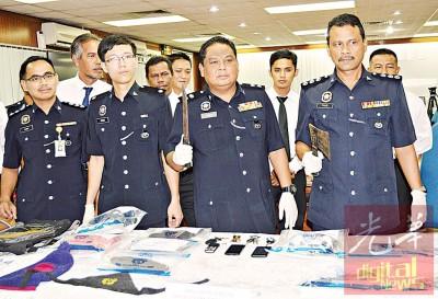 阿萨哈(右2)展示嫌犯闯入商店抢劫时,手上持着的巴冷刀或斧头。