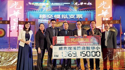 叶进煜(左3)移交模拟支票给李超瑞(右3),黄荣盛(左4)见证,伴随者为陈宝珠、林秀殷、庄杰江和李兴前。