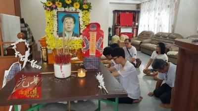 3名儿子跪在父亲杨炳富灵柩前默哀。