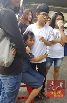 遗孀看着丈夫灵柩伤心欲绝,抱着二儿子耀锋哭成泪人,亲友在旁安慰。