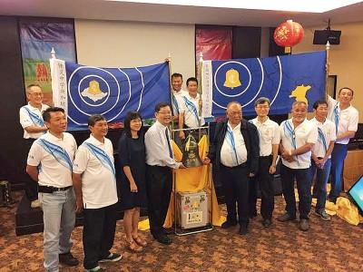 周昌江(右5)传递纪念铜钟给锺灵中学新加坡校友会会长范文斌(左4)。