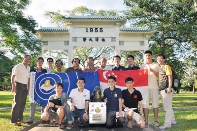 新加坡南洋理工大学锺灵学生与百年校庆纪念铜钟于前南洋大学大门前合影。