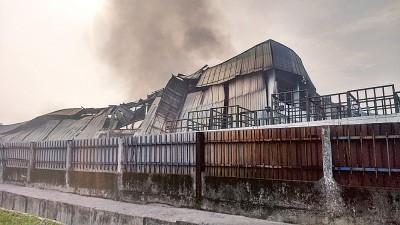 厂废墟堆仍然冒出黑烟,消防人员继续灌水,坐策安全。