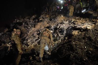 搜救人员入黑后仍在客机残骸搜索。(法新社照片)