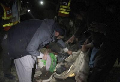 搜救人员将焦尸放入尸袋。