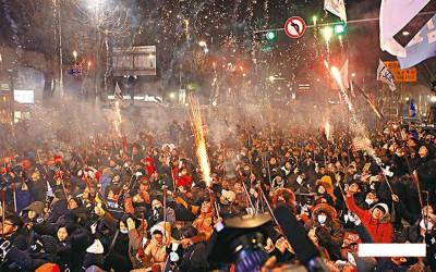 韩国国会通过朴槿惠弹劾案后,星期六于首尔抗议的群众放烟火庆祝,连要求它们就下台。