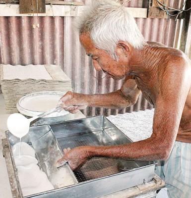 杨景明生前示范将米浆调制成水粉的过程。(档案照)