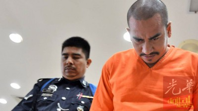 被告在庭内与其他案件被告轻松交谈,不过被押出法庭面对媒体镜头时却一直低头。
