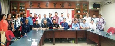商会代会长洪宝德(坐者右4)赠送纪念品予警方,由谢众盛(坐者左4)代表接领,并由商会众董事陪同。