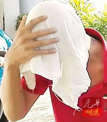 吴日益以布遮脸。