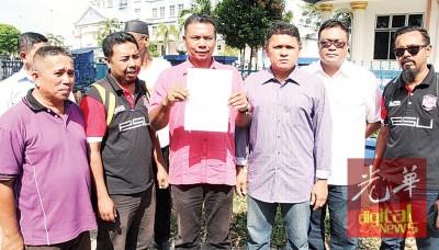 鲁斯里(右4)在巫统区部代表陪同下到威中警局报案。