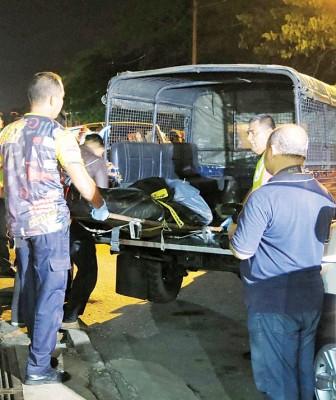 警方在完成搜证工作后,把死者抬上警车。