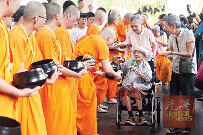 步履困难之老佛教徒在家人陪伴下到供僧。