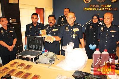 阿都嘉化(左4)与安华奥玛(左3)、黄亚添(右1)及颜永俊(左1)一同展示起获的毒品。