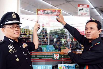 """岑振强(左)以及海尼也安达花园之7-11有关便民商店贴上""""一度装置闭路电视进行24时监控""""的贴纸。"""