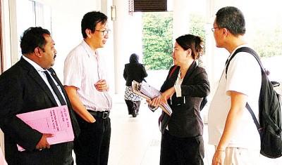 被告李伟泰(译音,右1者)目前已保外候审,一身便装出庭闻讯。左1为其代表律师巴迪班。