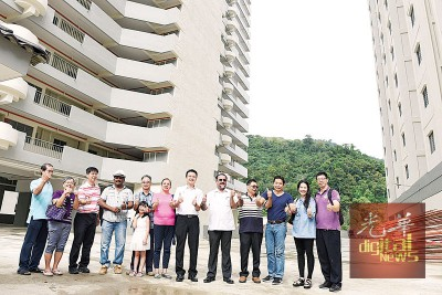 佳日星(左8)及杨顺兴(左7)在多名屋主的陪同下,巡视已经完成复兴工程的大华高原2A组屋。