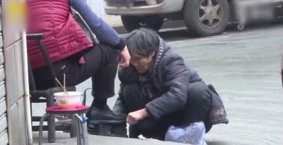 李荣玉在路边替人擦鞋。