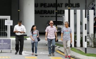 潘俭伟(右起)、林立迎与拉慕(左)周六离开警局。