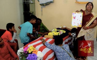 死者妻子乌莎(右)看著孩子们早前为爸爸准备的生日卡,在丈夫的灵柩前痛哭。