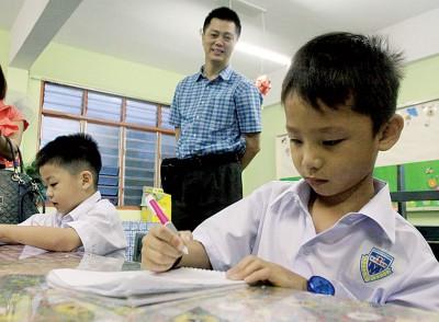 张立洋在学习书写名字,后为父亲张振亿,右为张伟善。