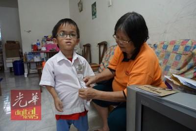 陈有存终于可以实现心愿,穿上校服到樟仑育民华小上课了! 图为其祖母陈玛利雅为小有存准备新校服,即将于周日开始上课了。