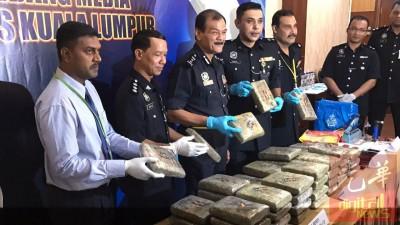 阿都哈密(左3)和下属展示起获的块状大麻和其他软性毒品。