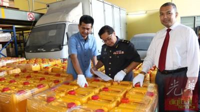 赛夫利占(右)与苏海米(中) 展示该局执法人员充公的回收食油桶。左为阿末阿拉祖丁。