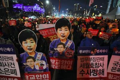 示威者高举印有朴实槿惠图像的口号牌。(法新社照片)