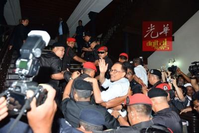 安华在大批警员包围下,不断向支持者挥手示好。