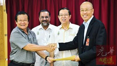 拿督黄伟国(左1)在首长林冠英(右2)和槟房屋委员会主席佳日星(左2)见证下,移交委任书予石礼兴。