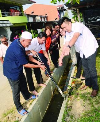 孙意志(左2)连片居民投诉后视察水沟积水问题。