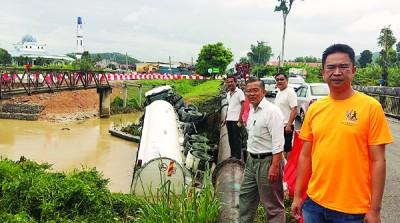 拖格油槽车撞落仁保河,车身脱落,司机受伤,而张聒翔(右起)及周世扬到场了解情况。