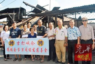 高高的仑德教会紫津阁副总务王国荣(左4)表示移交救济金予受影响灾民。