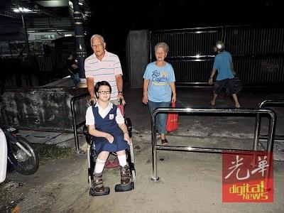 极乐寺临时拆除了其中一个铁栏杆,坐在轮椅上的残疾学生才得以进入学校。图为学生邢婕菱和她的公公邢定辉及婆婆许碧香。
