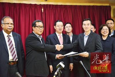 罗斯里(左2)及伍尚明(左4)在林冠英(左3)见证陪同下互换买卖合约。