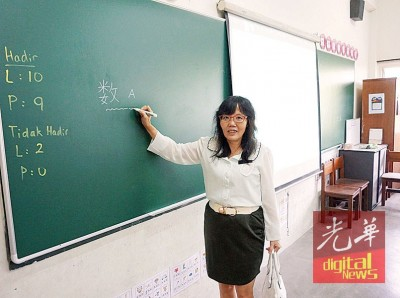 胡素彬介绍该校的电脑教学系统及环保黑板。